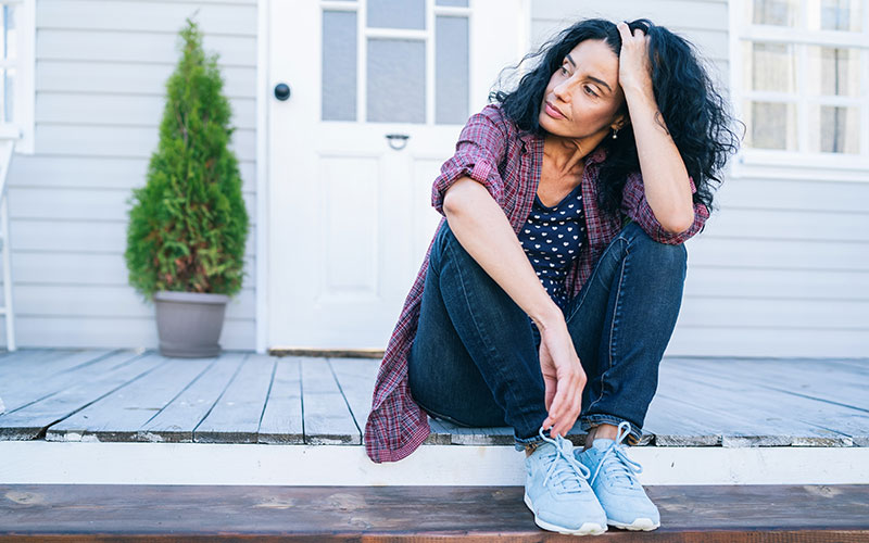 An older, dark-haired woman who may be experiencing or may be thinking about menopause. She sits outdoors on the porch of a white-washed house.